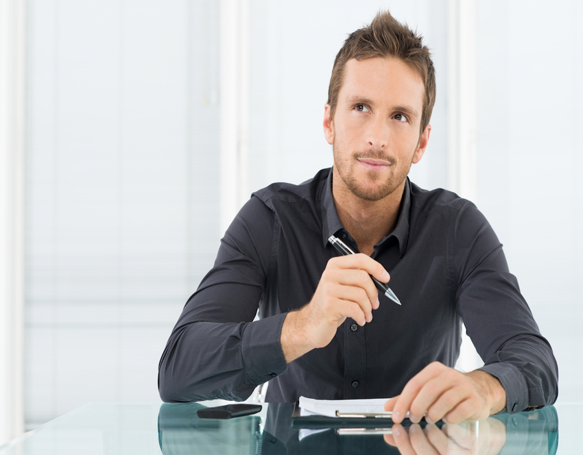 Young businessman thinking while writing.